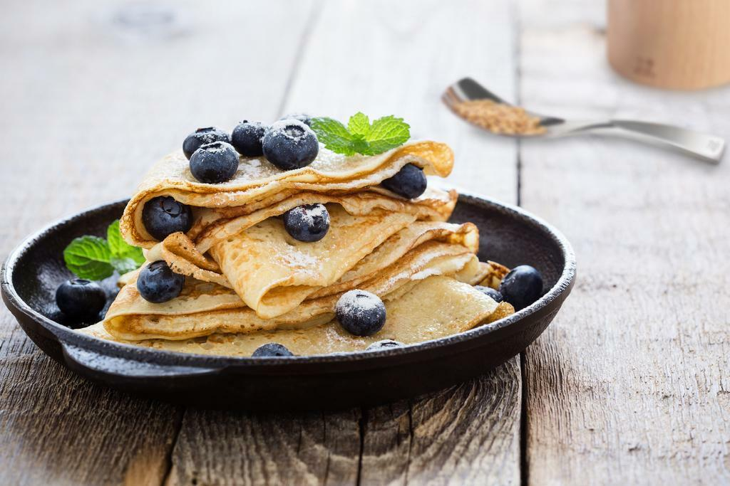 Crepes served with fresh blueberries and powdered sugar - Peugeot Saveurs